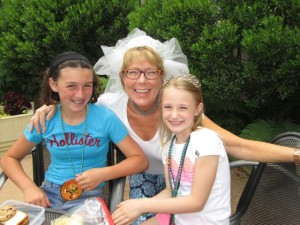 Lisa Tremper Hanover with granddaughters Peyton Powers (left) and Jillian Hanover kick off Art Camp with festive tiaras, veils, and bead necklaces.